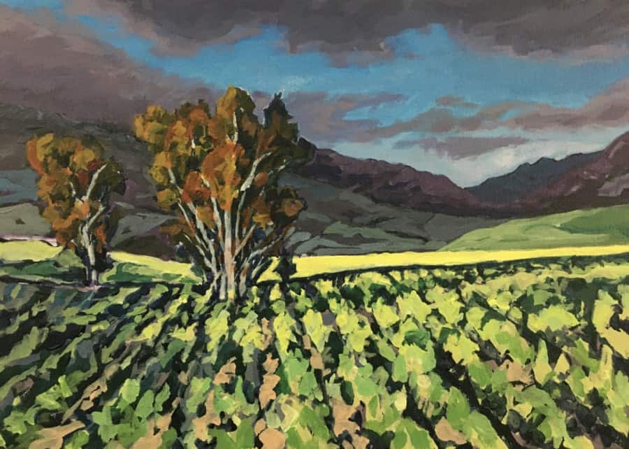 Expressionistic painting of 2 eucalyptus behind a vineyard with mountains in the background and a stormy sky.  Vivi brush strokes in greens, blues, purples, grey and brown.